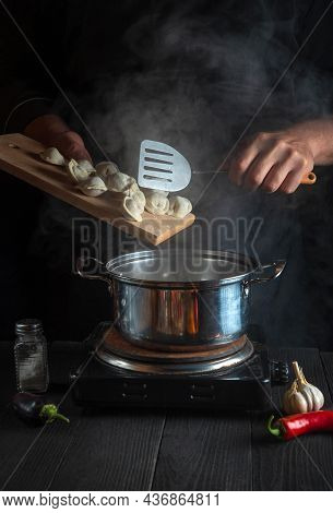 The Cook Cooks Meat Dumplings In A Saucepan In The Restaurant Kitchen. Close-up Of Hands Of The Cook