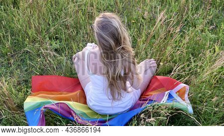 Lesbian Bisexual Blonde Woman Sitting On Lgbt Flag On Grass In White Dress. Support Of Non-tradition