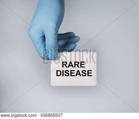 Rare Disease Concept. Text On White Paper In Hands In Blue Gloves.
