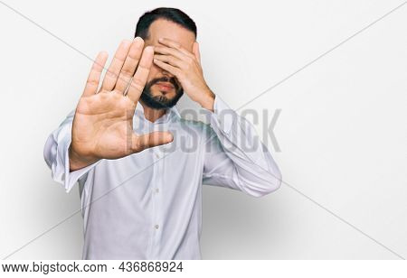 Young man with beard wearing business shirt covering eyes with hands and doing stop gesture with sad and fear expression. embarrassed and negative concept.