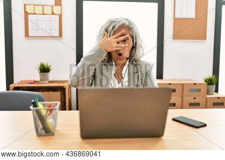 Middle age businesswoman sitting on desk working using laptop at office peeking in shock covering face and eyes with hand, looking through fingers with embarrassed expression.