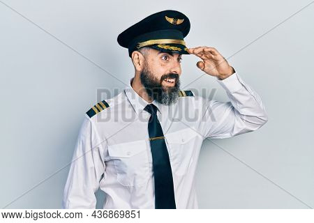 Young hispanic man wearing airplane pilot uniform very happy and smiling looking far away with hand over head. searching concept.