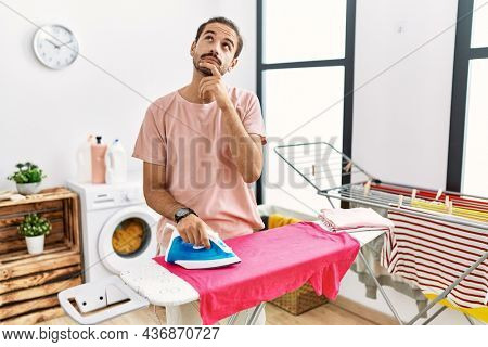 Young hispanic man ironing clothes at home with hand on chin thinking about question, pensive expression. smiling with thoughtful face. doubt concept.