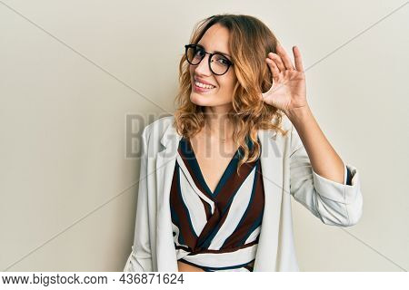 Young caucasian woman wearing business style and glasses smiling with hand over ear listening an hearing to rumor or gossip. deafness concept.