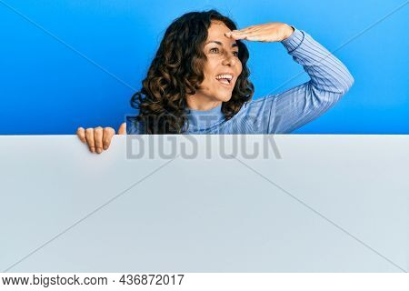 Middle age hispanic woman holding blank empty banner very happy and smiling looking far away with hand over head. searching concept.
