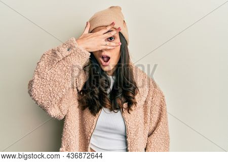 Young hispanic woman wearing wool sweater and winter hat peeking in shock covering face and eyes with hand, looking through fingers with embarrassed expression.