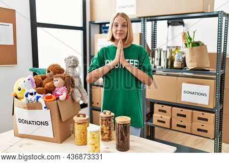 Young caucasian woman wearing volunteer t shirt at donations stand praying with hands together asking for forgiveness smiling confident.