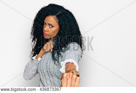Middle age african american woman wearing casual clothes punching fist to fight, aggressive and angry attack, threat and violence
