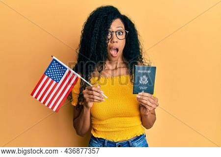 Middle age african american woman holding united states flag and passport in shock face, looking skeptical and sarcastic, surprised with open mouth