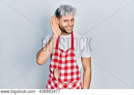 Young hispanic man with modern dyed hair wearing apron smiling with hand over ear listening an hearing to rumor or gossip. deafness concept.