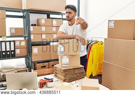 Young hispanic man working at small business ecommerce pointing with finger to the camera and to you, confident gesture looking serious