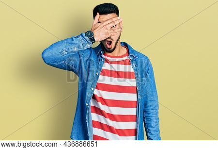Young hispanic man with beard wearing casual denim jacket peeking in shock covering face and eyes with hand, looking through fingers with embarrassed expression.