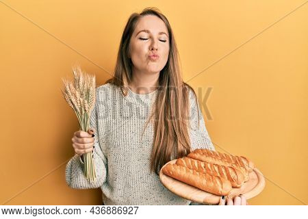 Young blonde woman holding homemade bread and spike wheat looking at the camera blowing a kiss being lovely and sexy. love expression.