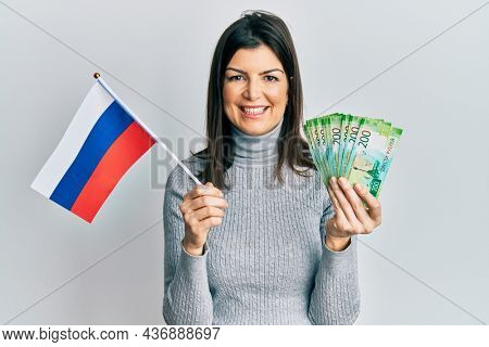 Young hispanic woman holding russia flag and rubles banknotes smiling with a happy and cool smile on face. showing teeth.