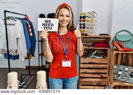 Young caucasian woman holding we need you banner hiring at retail shop smiling happy and positive, thumb up doing excellent and approval sign