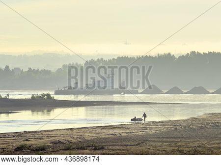 Novosibirsk Region, Siberia, Russia - 08.20.2020: A Fisherman Walks Along The Bank Of The Ob River.