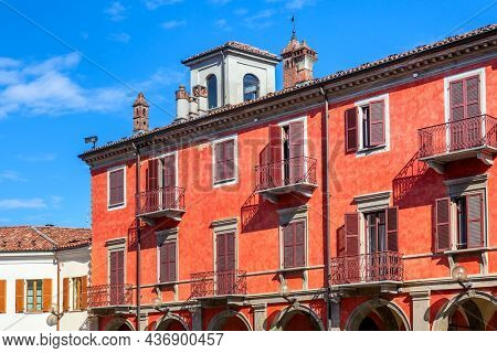 Facade of red two storey building with balconies and wooden shutters under blue sky in Alba, Italy.