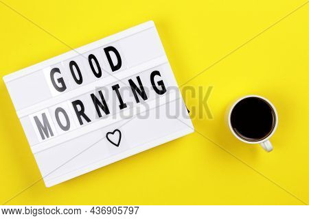Lightbox With Message Good Morning On A Yellow Table With A Cup Of Coffee