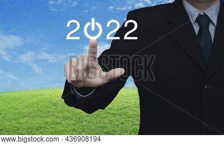 Businessman Pressing 2022 Start Up Business Flat Icon Over Green Grass Field With Blue Sky, Business