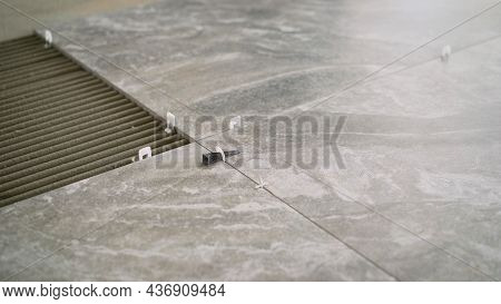 Laying Tiles On The Floor. Worker Placing Ceramic Floor Tiles On Adhesive Surface. Laying Ceramic Ti