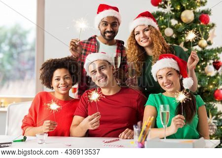 christmas, celebration and winter holidays concept - happy team in santa hats with sparklers and non-alcoholic champagne at corporate office party over christmas tree background