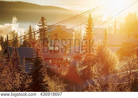 Frosty landscape in a ski resort. Early morning, sun in the background.