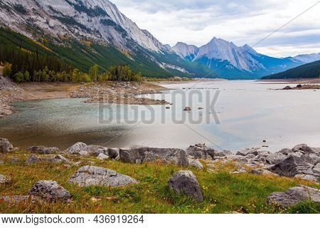 The Canadian Rockies. The shallow Medicine lake is fed by melted glacial waters. The lake is surrounded by mountain peaks. Autumn day