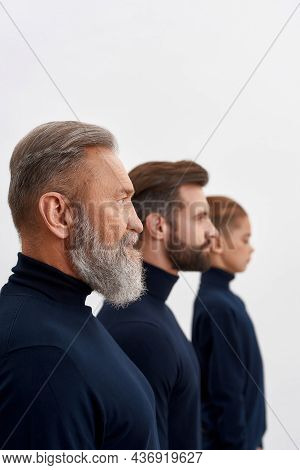 Narrow Vertical Shot Of Three Generations Of Caucasian Men Faces Isolated On White Studio Background