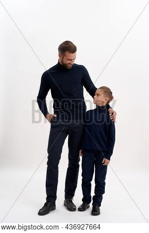 Narrow Vertical Shot Of Happy Young Caucasian Man Dad And Small Teen Son On White Studio Background