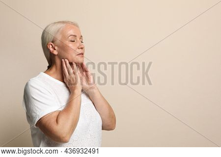 Mature Woman Doing Thyroid Self Examination On Beige Background, Space For Text