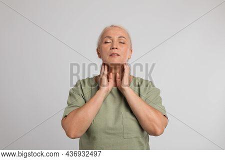 Mature Woman Doing Thyroid Self Examination On Light Grey Background