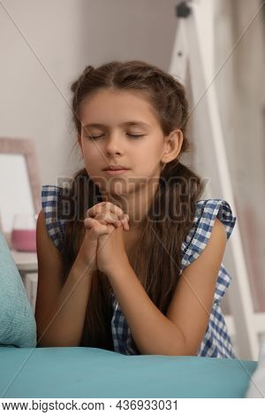 Cute Little Girl With Hands Clasped Together Praying At Home