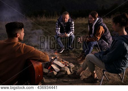 Group Of Friends Gathering Around Bonfire At Camping Site In Evening