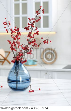 Hawthorn Branches With Red Berries On Table In Kitchen