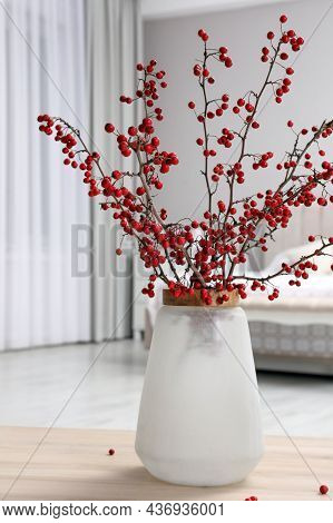 Hawthorn Branches With Red Berries On Wooden Table In Bedroom