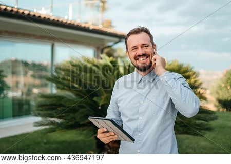 Man Using Smartphone Outdoor. Portrait Of Young Businessman Using Mobile Phone While Looking Away On