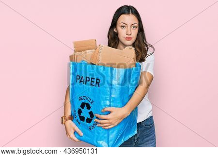 Young beautiful woman holding recycling wastebasket with paper and cardboard thinking attitude and sober expression looking self confident