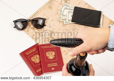 A Woman\'s Hand Opens A Bottle Of Red Wine With A Corkscrew, A Map Of The World, Two Passports, Mone