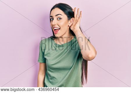 Beautiful woman with blue eyes wearing casual t shirt smiling with hand over ear listening an hearing to rumor or gossip. deafness concept.