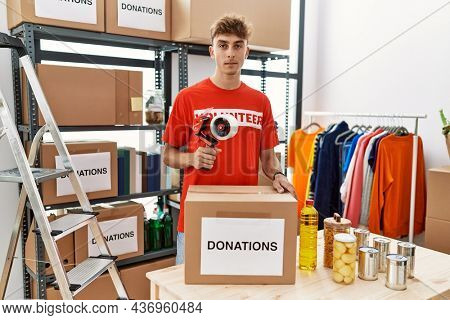 Young caucasian volunteer man packing donations box at charity center thinking attitude and sober expression looking self confident