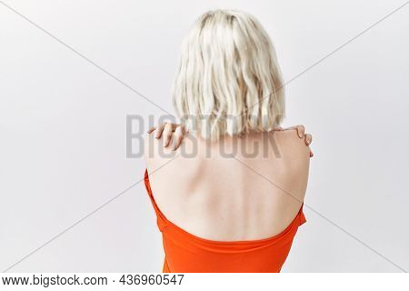 Young caucasian woman standing over isolated background hugging oneself happy and positive from backwards. self love and self care