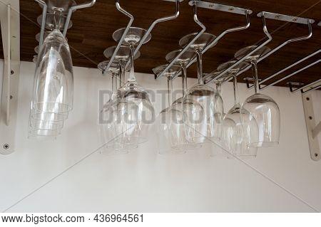 Wine Glasses Hanging In Holder. Organized Inside Cupboard. Home Interior Storage