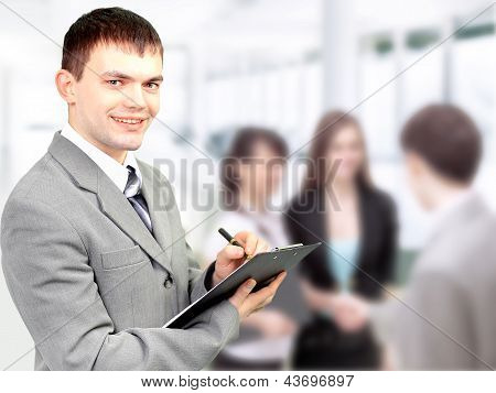 Portrait Of Confident Business Man Holding Document With Team In Blur Background