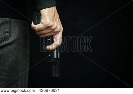 Criminal With Revolver In His Hand. Firearm For Defense Or Attack. Killer On Black Background. Man I