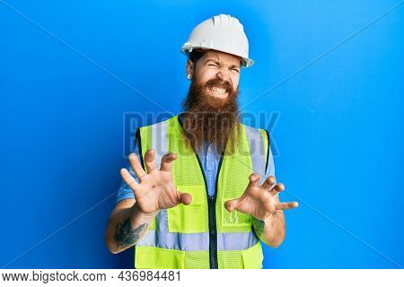 Redhead man with long beard wearing safety helmet and reflective jacket disgusted expression, displeased and fearful doing disgust face because aversion reaction. with hands raised