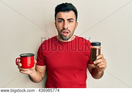 Young hispanic man holding cup of soluble coffee in shock face, looking skeptical and sarcastic, surprised with open mouth