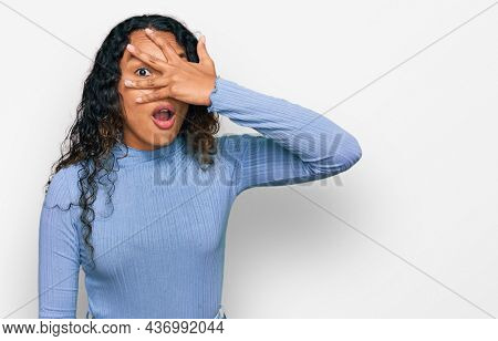 Young hispanic woman with curly hair wearing casual clothes peeking in shock covering face and eyes with hand, looking through fingers with embarrassed expression.