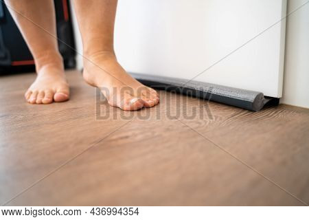Person Walking Barefoot Near Draft Excluder Under Door Blocking Cold Air From Traveling Around