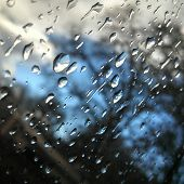Close up of raindrops on my window with the dark skies in the background poster