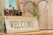 Rustic wooden WELCOME sign standing on a wooden shelf in front of a wood panel with a cut out heart offering a warm country welcome poster